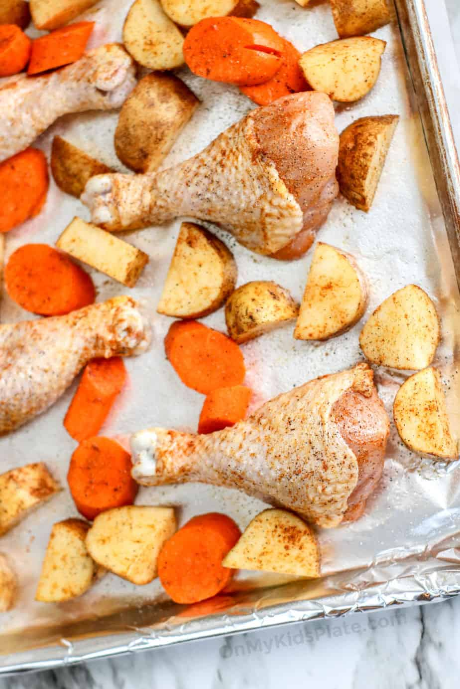 Chicken drumsticks and vegetables seasoned and spread on a rimmed baking sheet.
