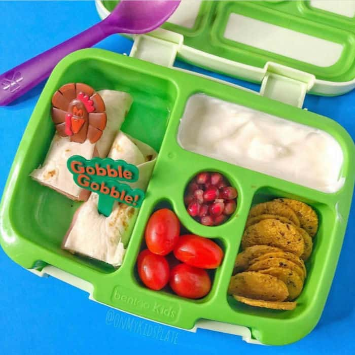 A bento lunchbox filled with tomatoes, pomegranate seeds, yogurt, wraps and sweet potato crackers