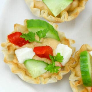 Close up of a party snack appetizer full of hummus, cucumber, red pepper and feta cheese.
