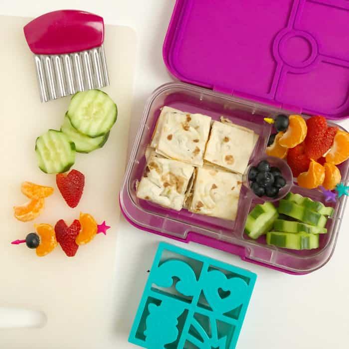A kid's bento lunchbox full of quesadilla, cucumbers, blueberries, oranges and strawberries shaped like hearts