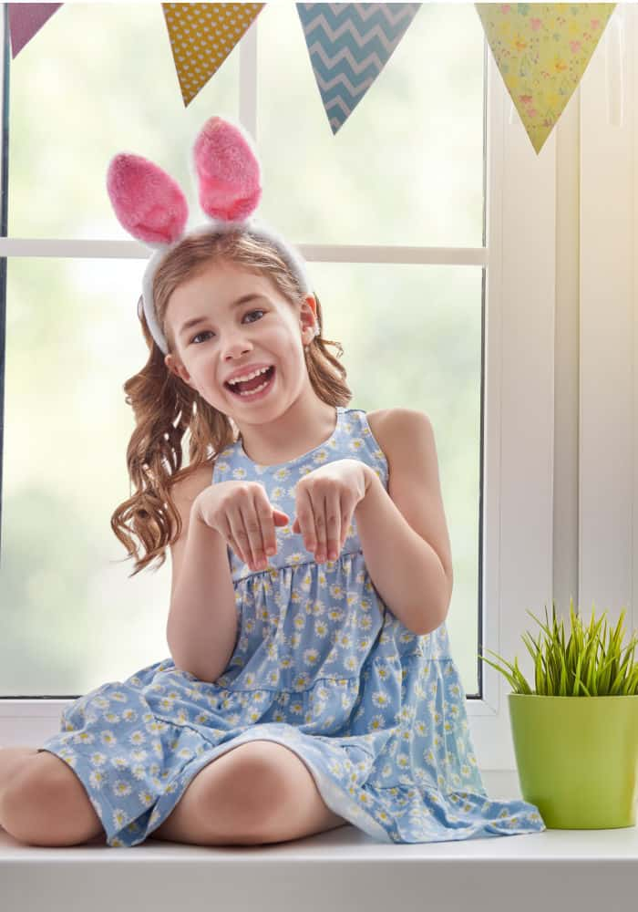 A little girl sitting in front of a window pretending to be a rabbit