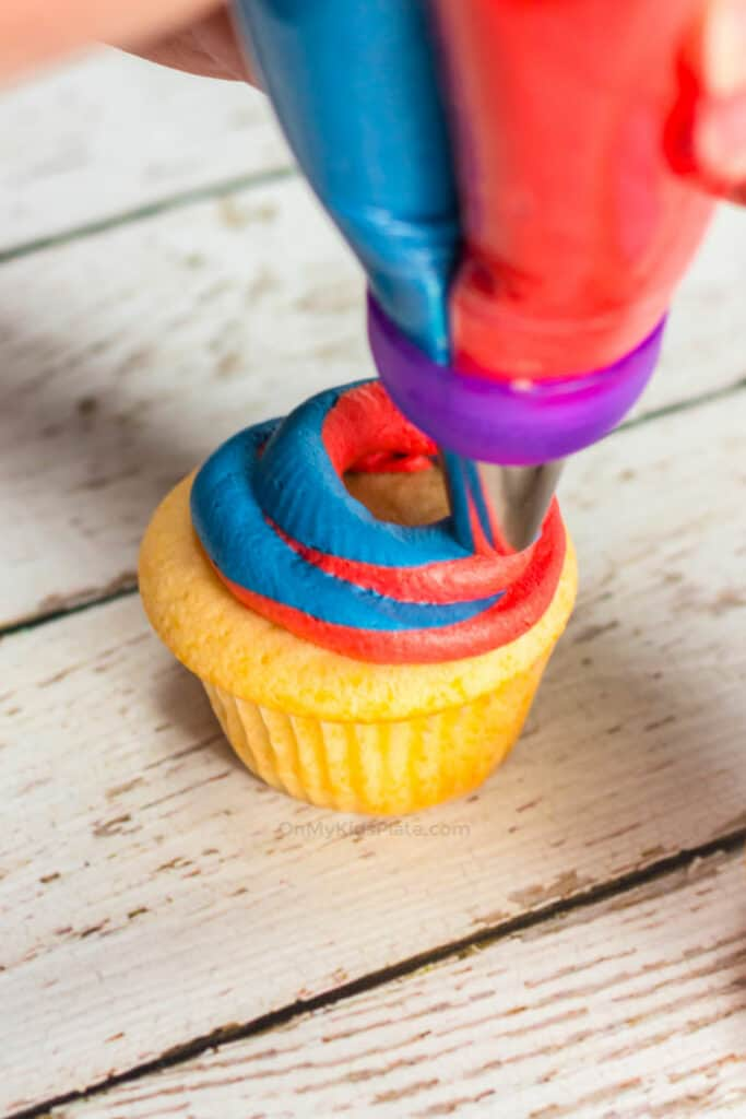 A cupcake being frosted with a swirl of red and blue frosting together