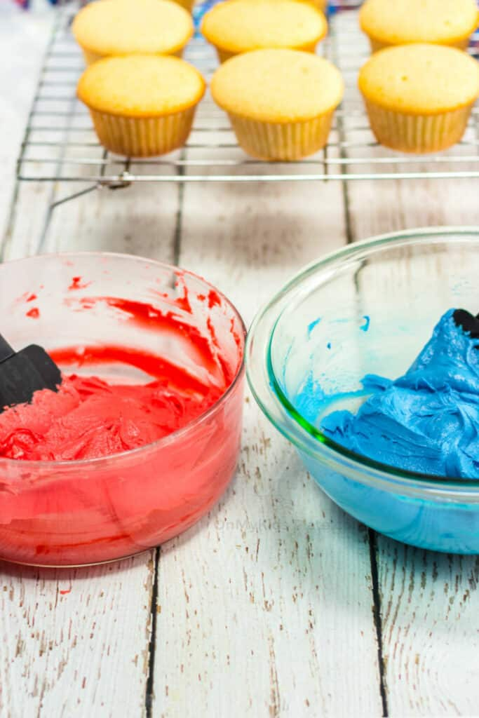 Red and blue frosting being mixed with cupcakes behind