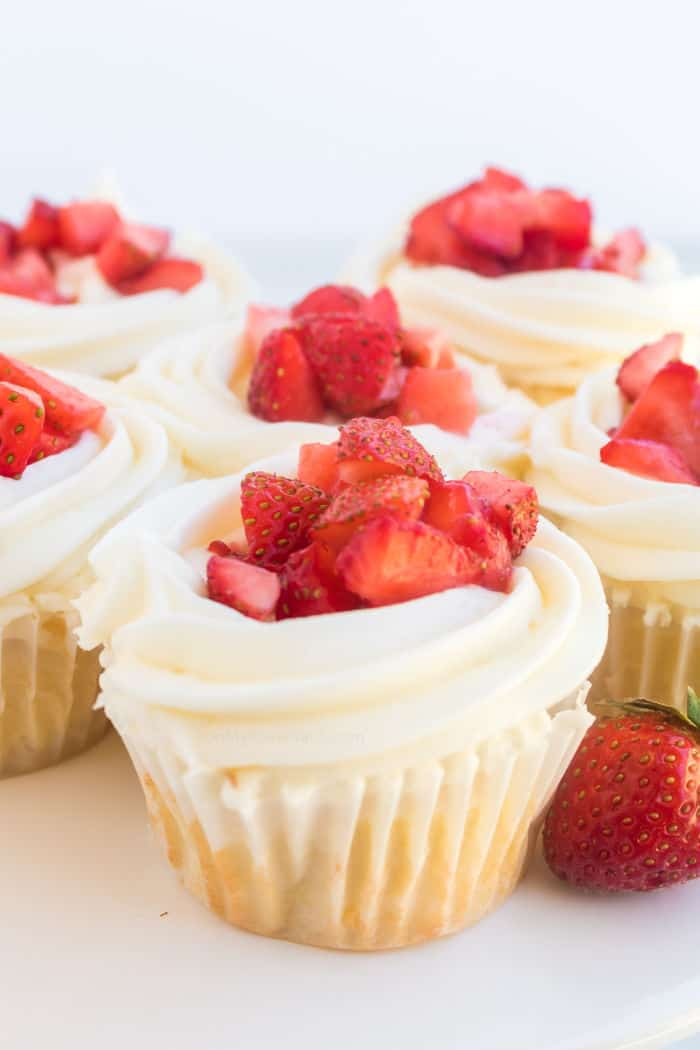 Several cupcakes frosted topped with fresh strawberry pieces