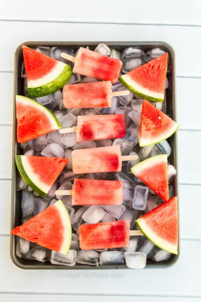 Watermelon popsicles are laid with slices of fresh watermelon on a tray of ice on a table.