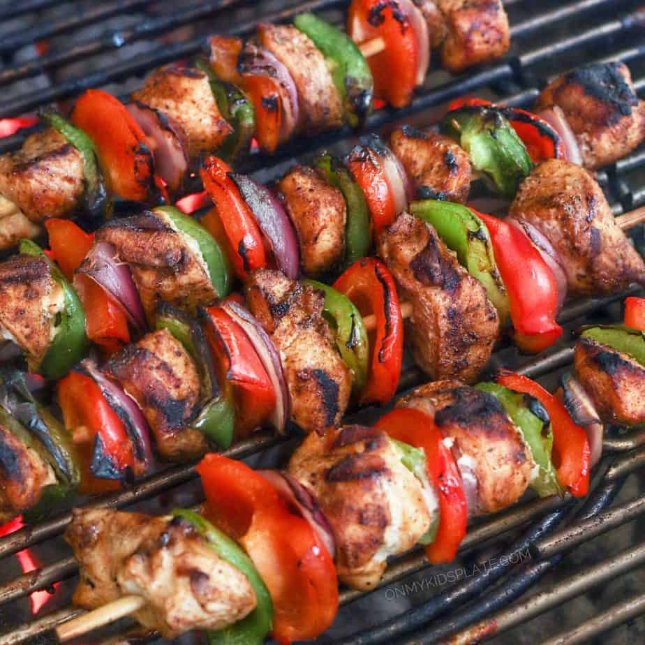 A close up view of chicken, peppers and onions threaded on skewers cooking on a grill.