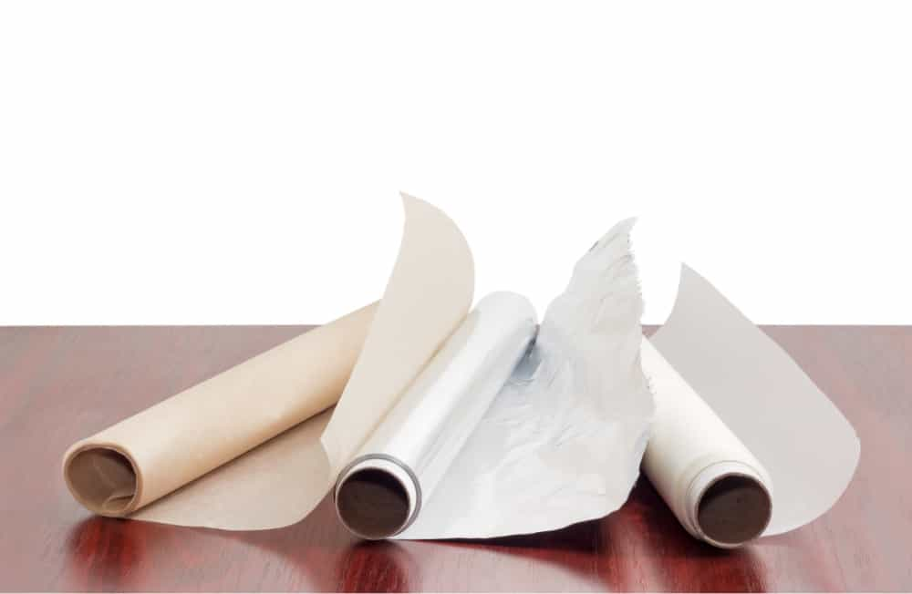 Two rolls of the various parchment paper and one roll of the aluminum foil for household use on a dark red wooden table on a white background