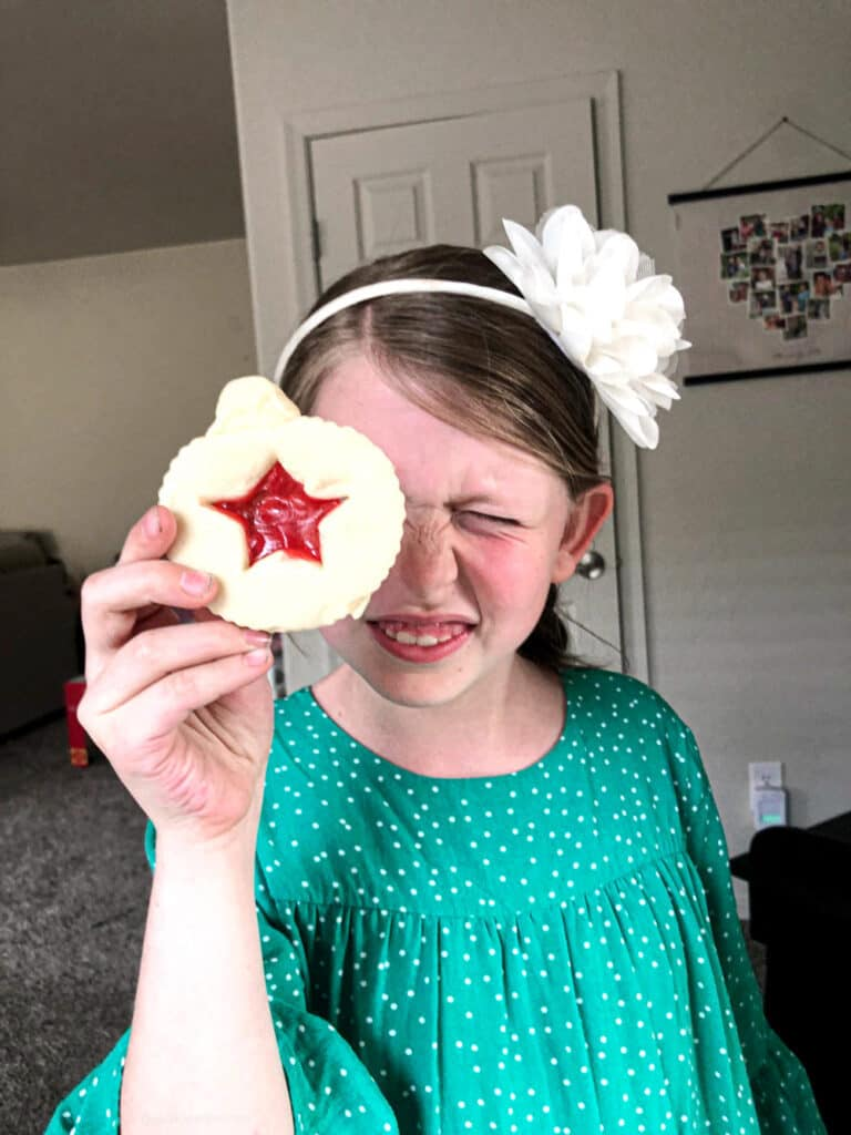 Girl holds stained glass sugar cookie up to her eye looking through it.