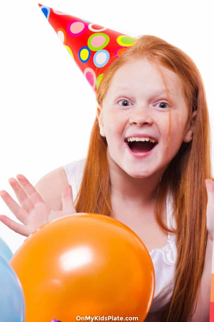 Girl laughing with birthday hat and balloons