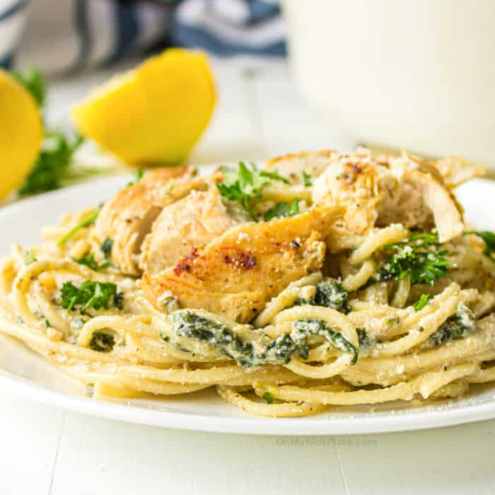 Chicken and spinach with spaghetti in a cheese sauce with lemon in the background