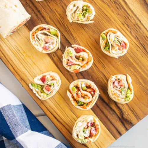 Cutting board from overhead with rolled tortilla pinwheels full of vegetables and a creamy sauce.