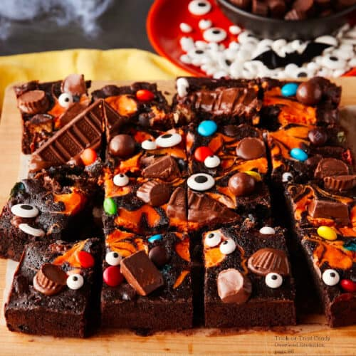 Side view of brownies covered in an orange cream swirl, chocolate candy and candy eyes for Halloween on a cutting board
