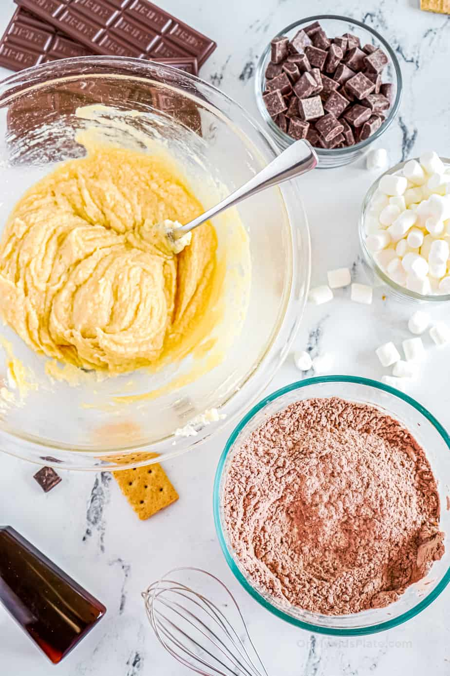 Two bowls with wet and dry cookie dough mixtures ready to be mixed and other cookie ingredients such as chocolate and marshamallows in bowls nearby.