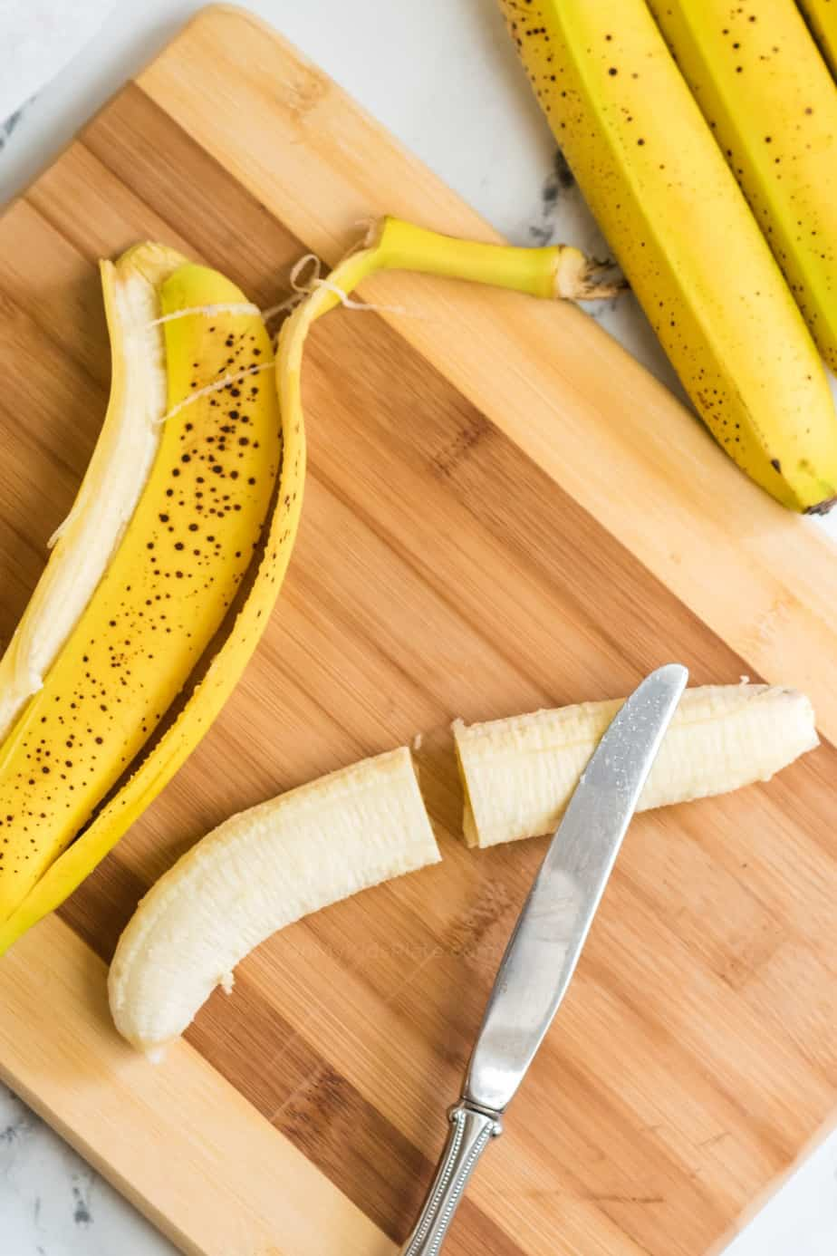 Banana being sliced in half with a knife on a cutting board next to the peel and more bananas