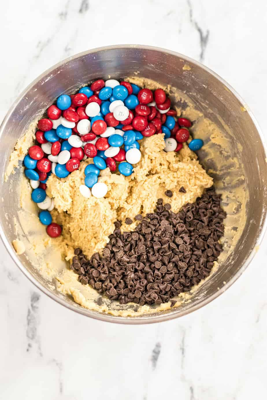 Cookie dough with red white and blue M&Ms and chocolate chips in a bowl.