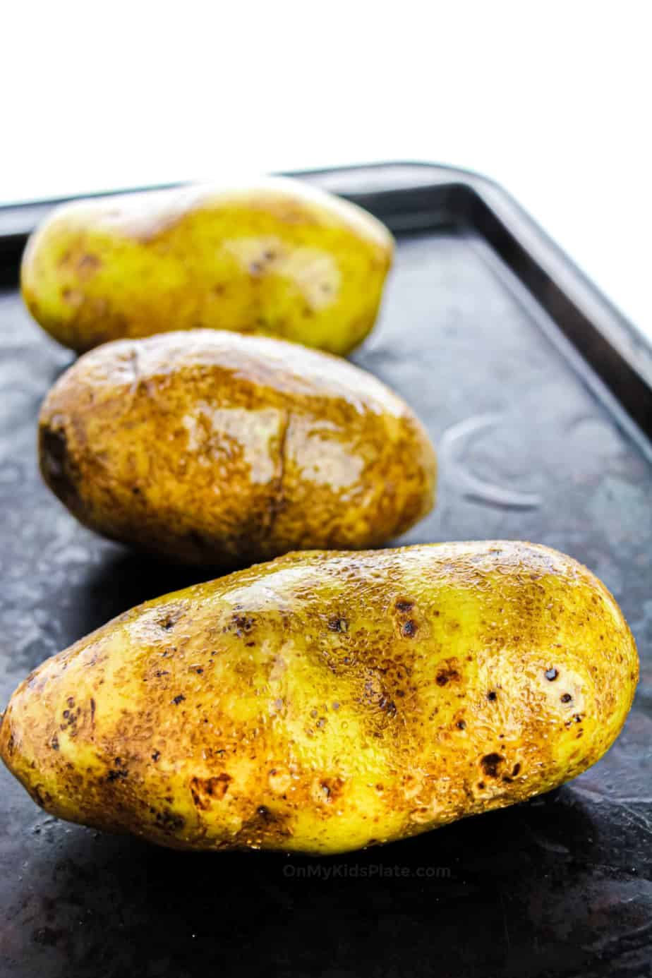 Three potatoes on a baking sheet rubbed with oil