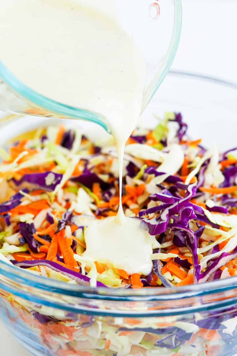 Pouring dressing over cabbage and carrot mixture in a clear bowl from the side.