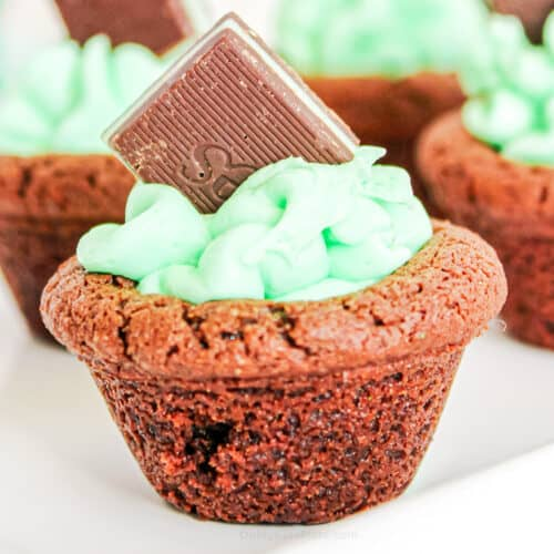 Close up of a chocolat4e cookie cup filled with frosting and a chocolate mint candy on a serving tray