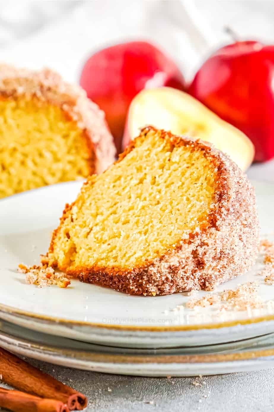 Slice of cider doughnut cake with on a plate with apples in the background