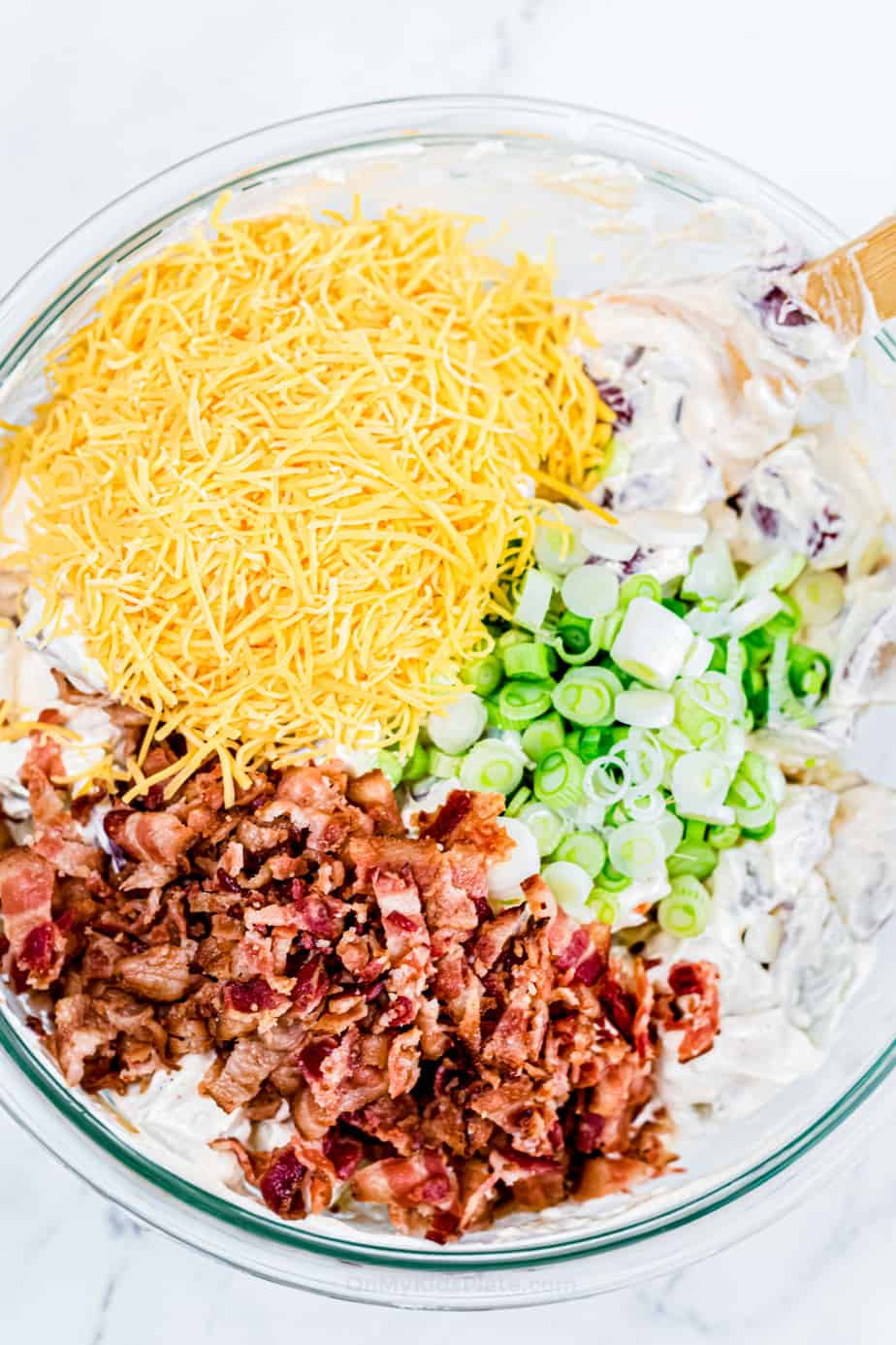 Cheese, bacon and green onions being mixed into potatoes cover in dressing in a bowl.