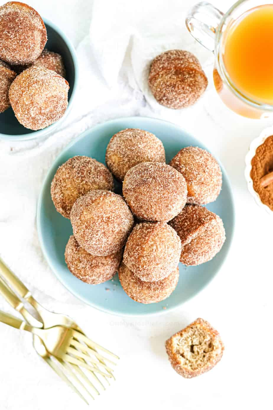 Plate of doughnut holes covered in cinnamon sugar from overhead with a glass of apple cider, forks and a second bowl of doughnut holes nearby on the table
