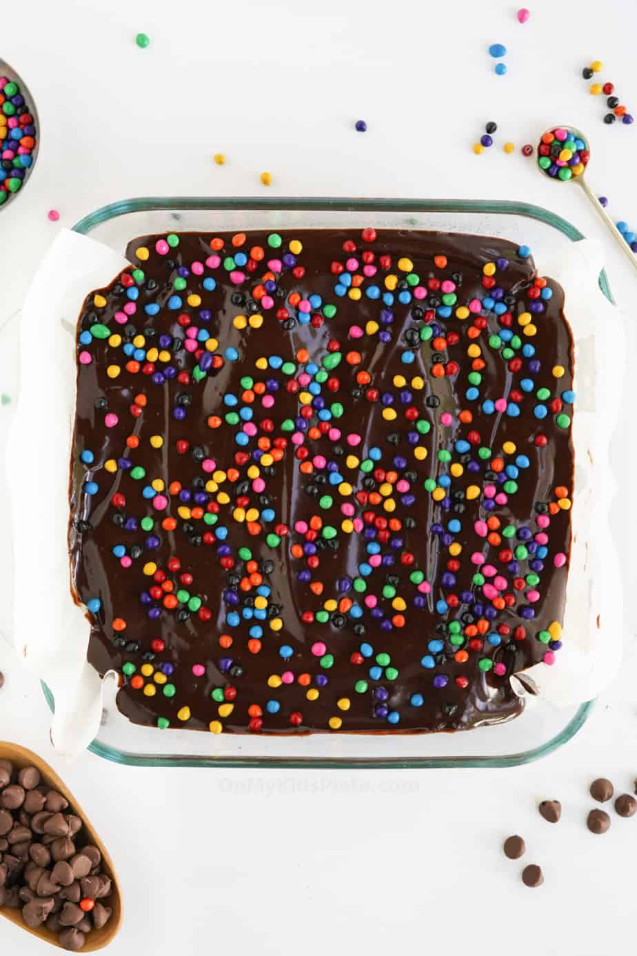 Chocolate brownies in the pan from overhead covered in chocolate frosting and rainbow crunch sprinkles.