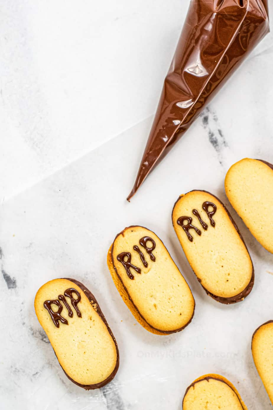 Decorating Milano cookies writing RIP in chocolate to make gravestones.