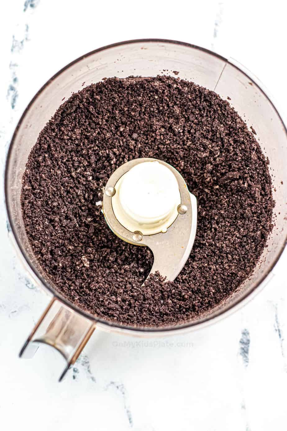 Oreo crumbs crushed inside of a food processor.