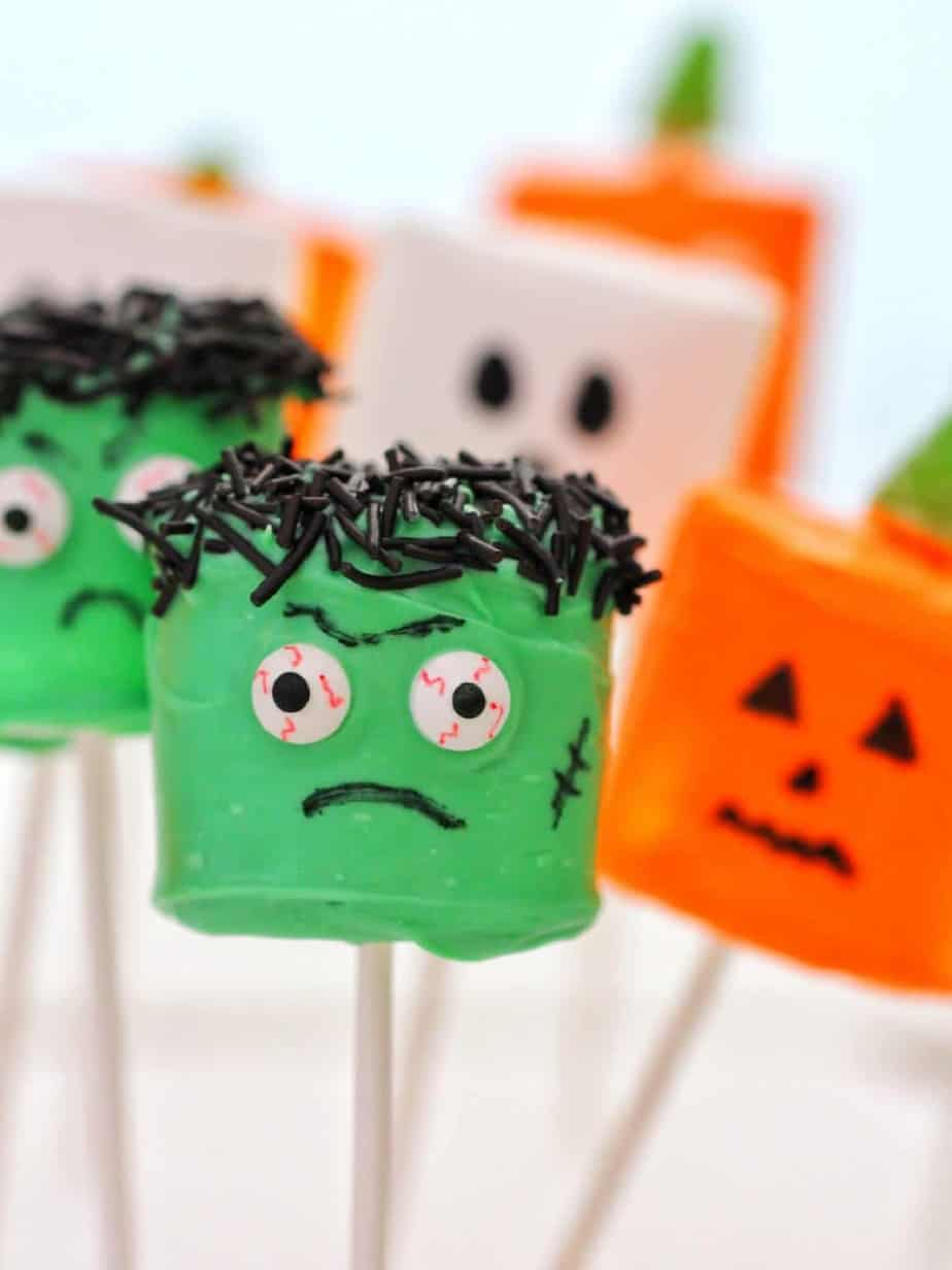 Marshamallows on sticks decorated like monsters, ghosts and jack o lanterns.