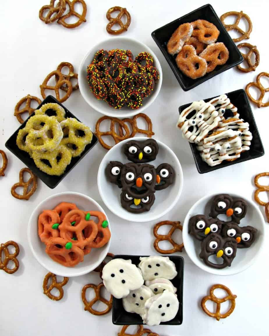 A variety of chocolate dipped pretzels in bowls decorated like owls, mummies, pumpkins, ghosts and with sprinkles