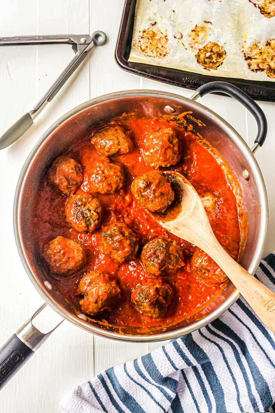 Meatballs in a pan in pasta sauce being stirred with a spatula