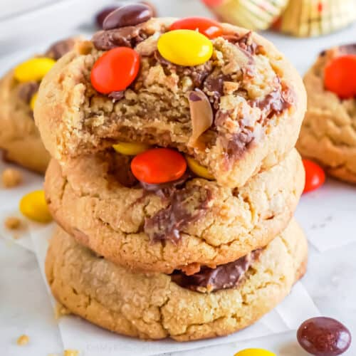 Close up stack of reese pieces topped cookies with the top cookie missing a bite