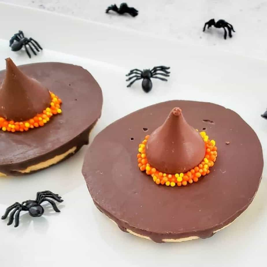 A chocolate kiss candy on top of a cookie decorated to look like a witch hat.
