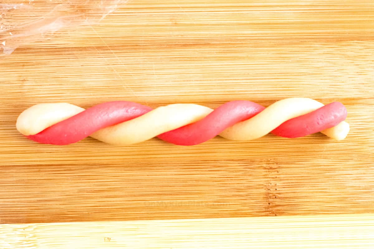White and red cookie dough twisted into a rope on a cutting board