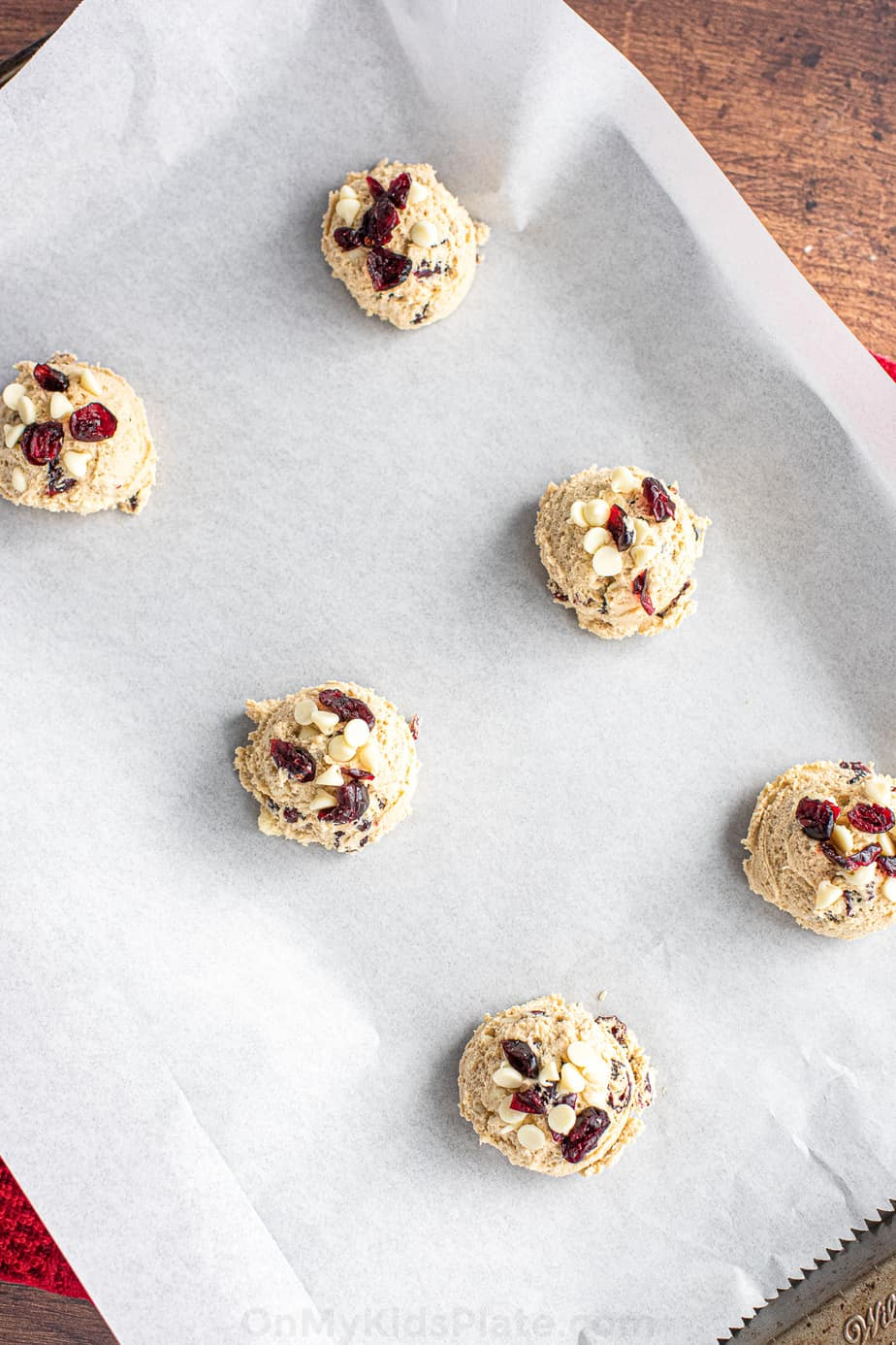 Raw cookie dough full of dried cranberries and white chocolate chips on a parchment lined baking pan zoomed in and tilted to the side.