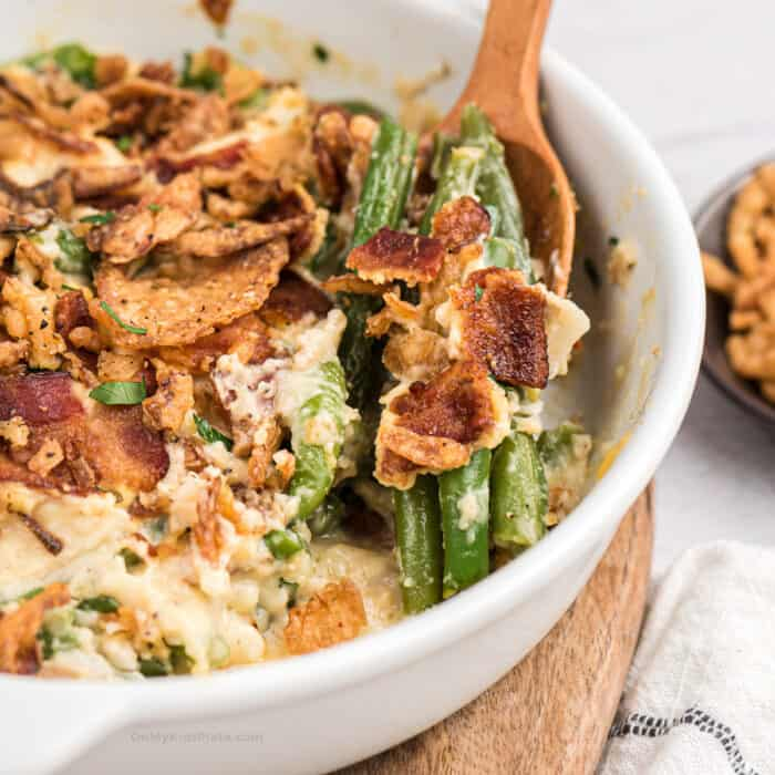 Close up of spoon scooping green bean casserole with bacon from a casserole dish