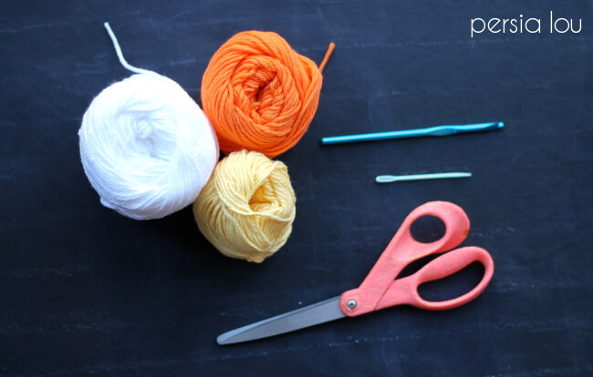 candy corn bag supplies on a black surface: yarn, needle, crochet hook, and scissors