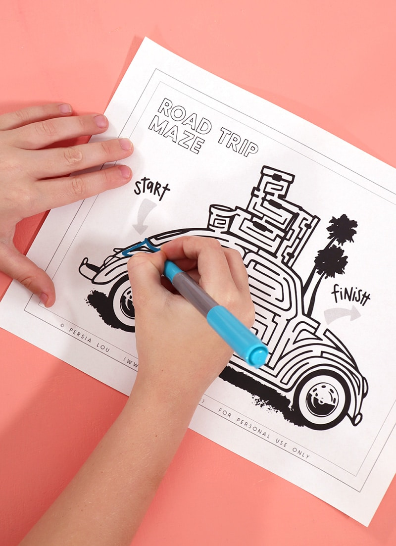 kids hands drawing in free printable road trip themed maze activity
