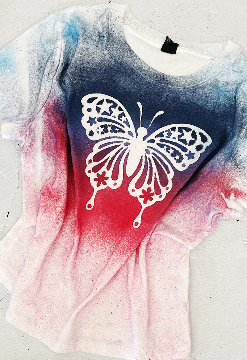 White t-shirt that has been spray dyed with red and blue dye around a white butterfly design.