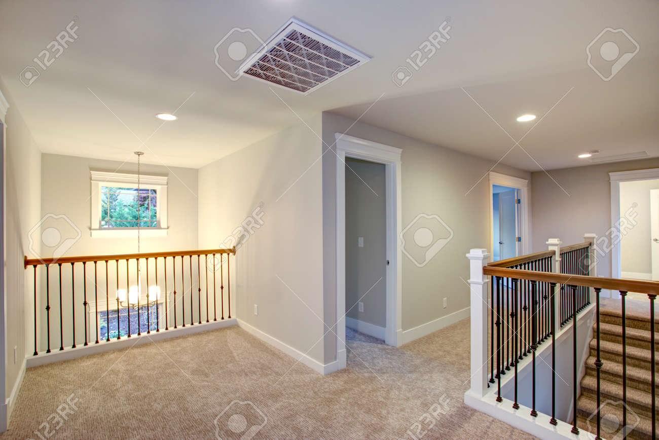 Empty New Construction Home Interior Features Second Floor Landing | Light Grey Carpet Stairs | Industrial | Runner | Modern | Grey Vinyl Flooring | Living Room