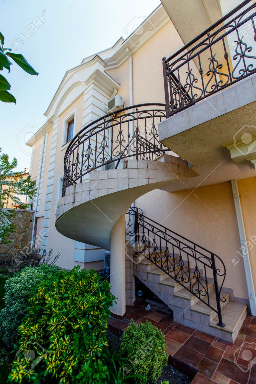 A Concrete Spiral Staircase With Wrought Iron Railings Leads | Wrought Iron Spiral Staircase | Wood | Gothic | Small | Mezzanine | Internal
