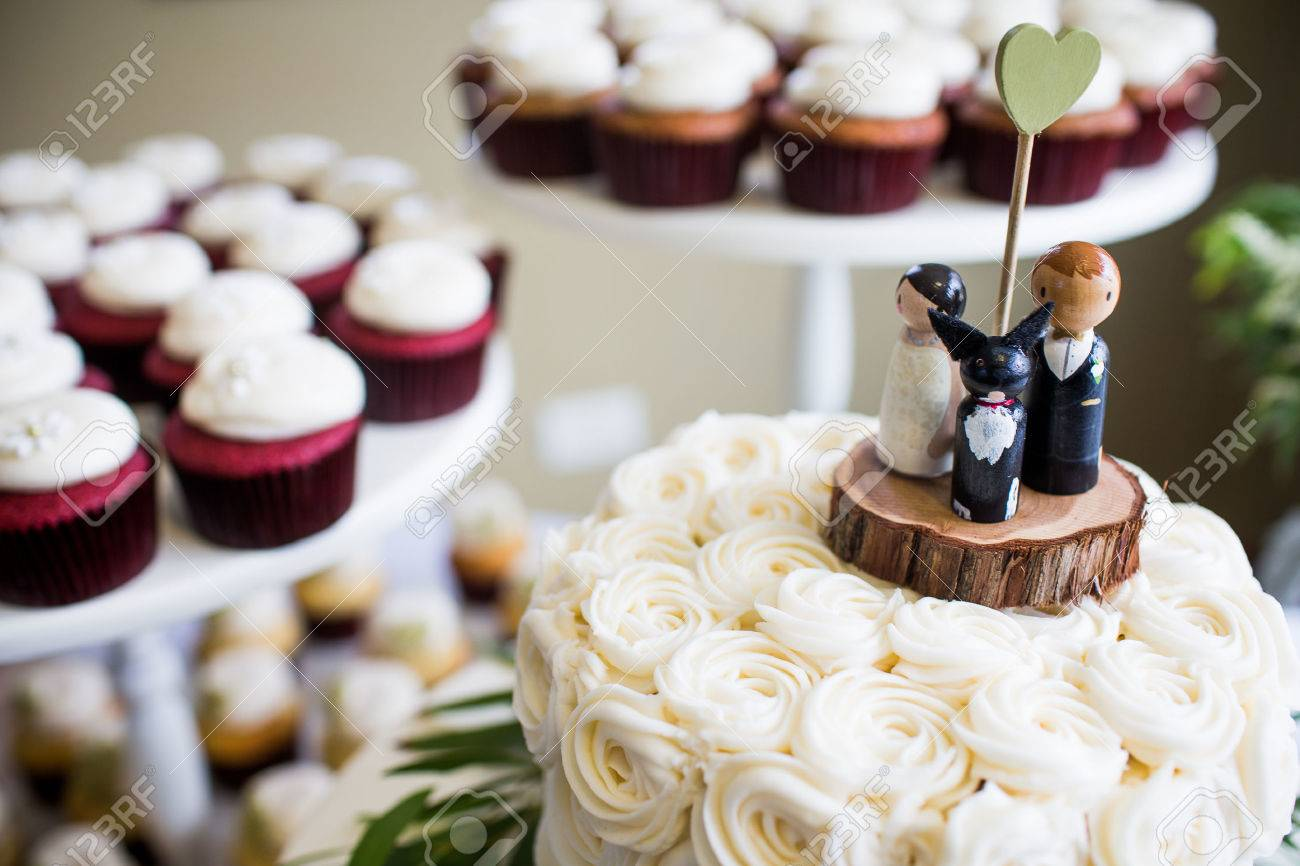 Cute Bride  Groom  And Dog Wedding Cake Topper With Cupcakes   Stock     Cute bride  groom  and dog wedding cake topper with cupcakes in the  background Stock