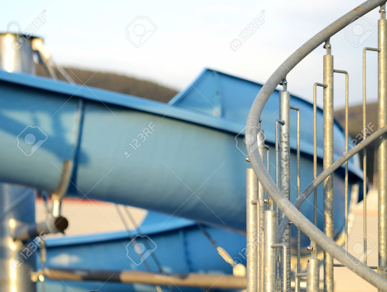Detail Of Spiral Stairs To Blue Water Slide At Sunset Stock Photo | Spiral Staircase With Slide | Modern | 1930'S | Interior | Cool | Stainless Steel Spiral