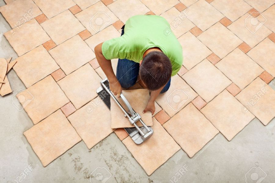 Man Laying Ceramic Floor Tiles Working With A Cutter Device     Man laying ceramic floor tiles working with a cutter device   top view  Stock Photo