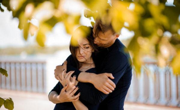 Bir adam çatık bir kıza sarılıyor