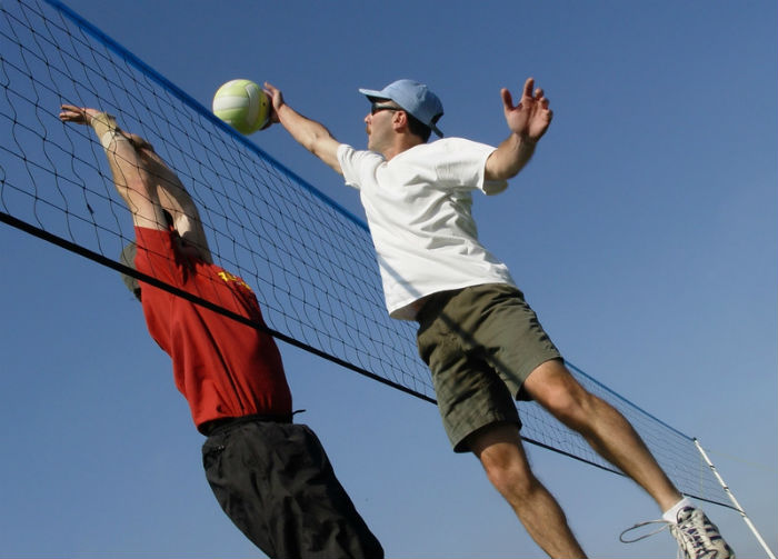Anaheim man playing volleyball with a friend
