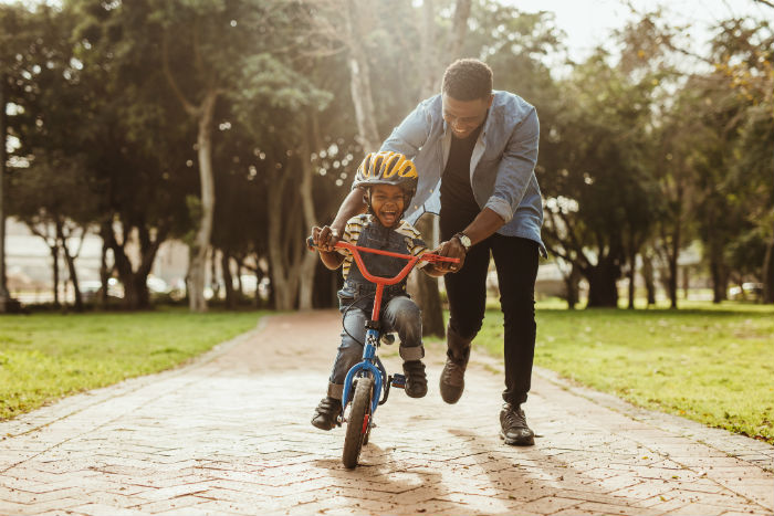 Father teaches son to ride bike