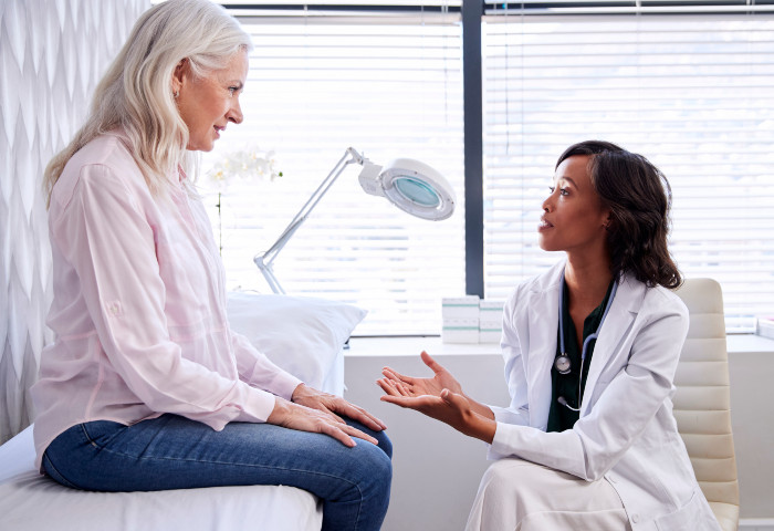 A elderly woman meets with a stem cell doctor for a consult