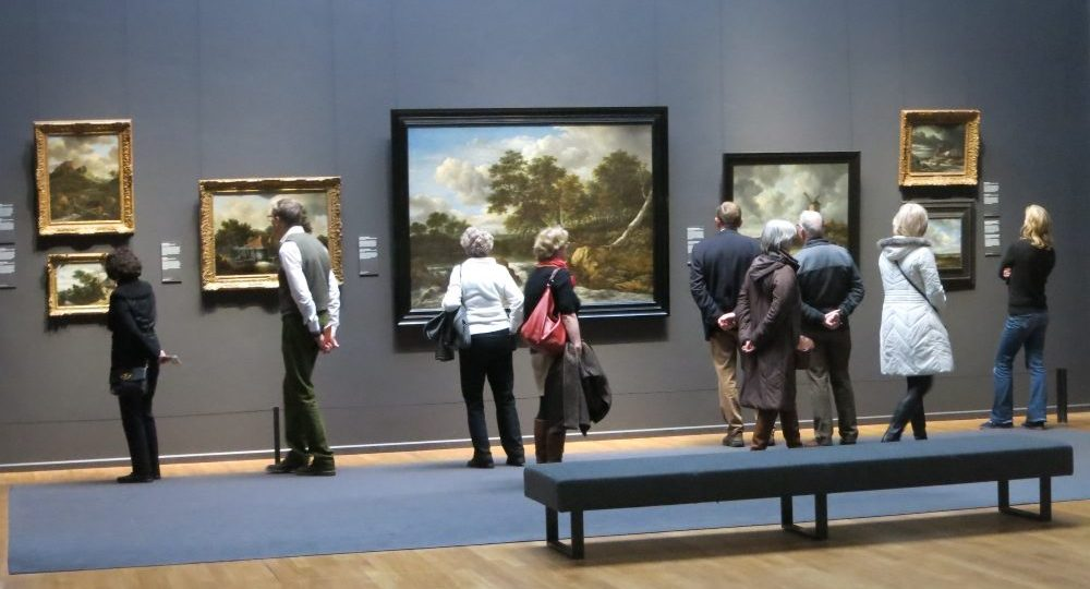 A row of Golden Age landscapes on the wall, and 9 visitors, backs to the camera, viewing the paintings.