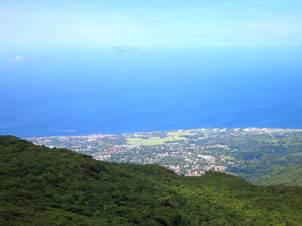 a view down over land and villages far below and the very blue sea beyond, blending with the blue sky.